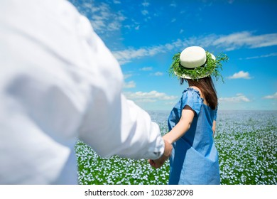 Young happy beautiful pregnant couple in linen field