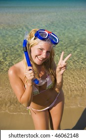Young happy beautiful summer woman with swimming mask and snorkel preparing to dive in blue sea