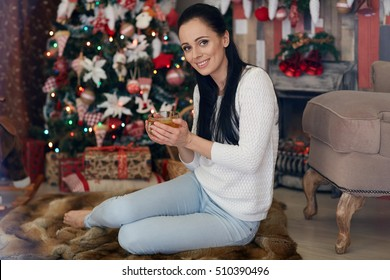 Young happy beautiful woman with cup of tea sits near Christmas tree in the room of the house. Merry Christmas and New Year.