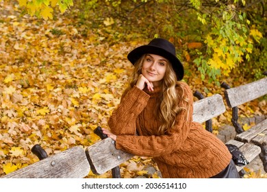 Young happy beautiful woman with curly hair wearing black hat and sweather having good time in autumn park