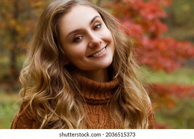 Young happy beautiful woman with curly hair wearing sweather having good time in autumn park