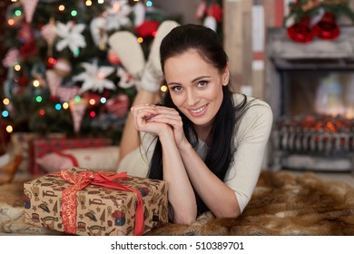Young happy beautiful woman with gift box lies near Christmas tree in the room of the house. Merry Christmas and New Year.