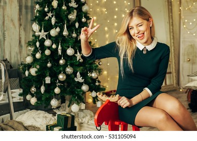 Young happy beautiful woman with gift boxes sits near Christmas tree in the room of the house