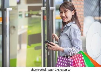 Junge glückliche schöne Frau, die bunte Einkaufstaschen bei der Eröffnung der Glaseinkaufstür hält