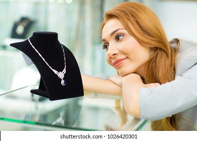 Young happy beautiful woman looking at the luxurious diamond necklace smiling joyfully shopping at the jewelry store copyspace affordable dreaming consumerism happiness emotions lifestyle retail.