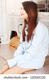 Young happy beautiful woman sitting on kitchen counter in men's shirt
