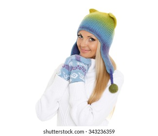 Young happy beautiful woman in winter clothes stands on a white background.