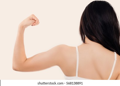 Young happy beauty healthy Asian woman flexing her arm muscle, strong lady.