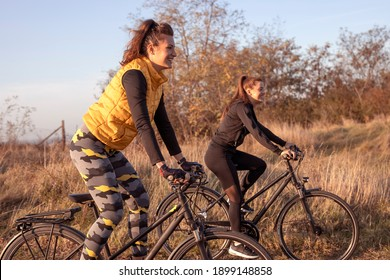 Young and happy best female friends in sportswear riding mountain bikes together in nature