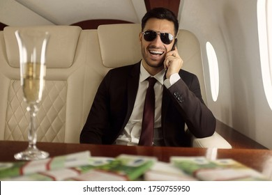 Young happy billionaire on board of his private jet sitting at table with champagne and euros in cash, talking on phone and laughing happily, enjoying financial success