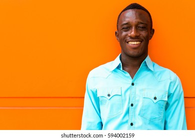 Young happy black African man smiling while leaning against orange painted wall