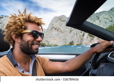 Young happy black man with dread locks wearing sunglasses sitting in the convertible car.