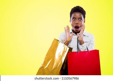 young happy black woman holding shopping bags