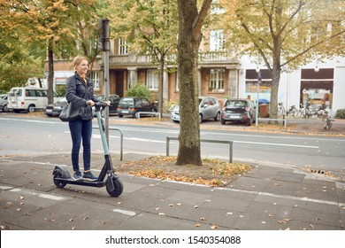 Young happy blond woman riding an electric scooter in the city in autumn, side view