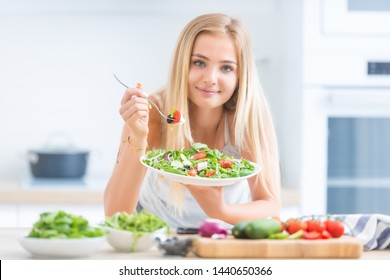 Young happy blonde girl eating healthy salad from arugula spinach tomatoes olives onion and olive oil.