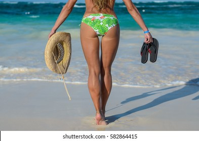 Young happy blonde woman stands during her vacation at the seashore. She wearing a swimsuit. The woman holds in her hands a straw hat and slippers.