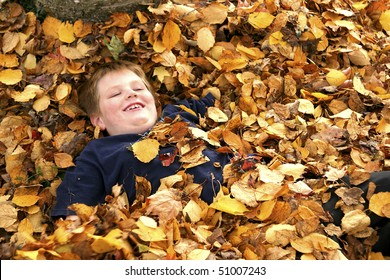 Young Happy Boy in Pile Of Autumn Leaves