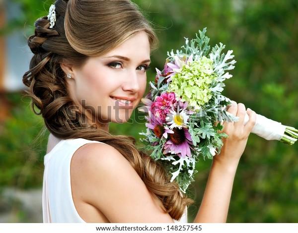 Junge glückliche Braut mit BlumenBouquet