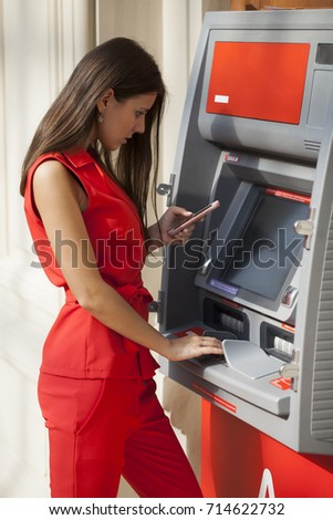 694297e19154 Young happy brunette woman in red dress withdrawing money from credit card  at ATM
