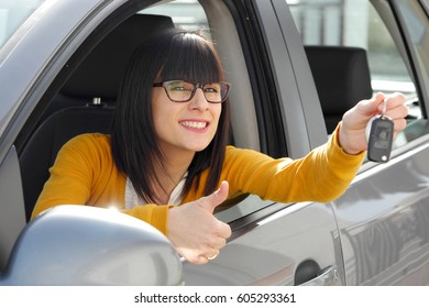 Young happy brunette woman showing the key of new car