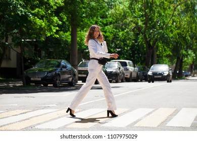 Young happy brunette woman in white business suit walking in the summer street