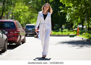Young happy brunette woman in white business suit and bag walking in the summer street