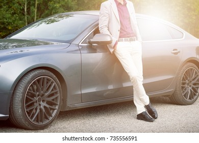 Young happy business man in the car. Man in a suits standing by the expensive sport car. Successful young man.
