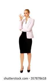 Young happy business woman shows OK sign.