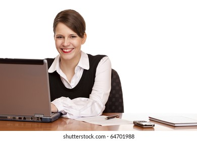Young happy business woman sits on desk and works on laptop. Isolated on white background.