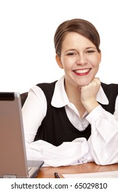 Young happy business woman sits on desk in office. Isolated on white background.
