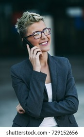 Young happy business woman standing in front of big modern building. She smiling and talking on her cell phone.