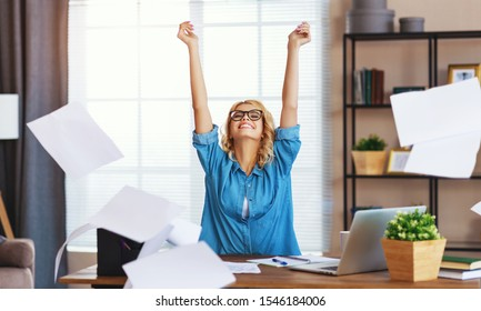 young happy business woman working on computer and  throws up   papers in home office