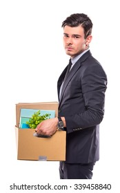 Young happy businessman with box for moving into a new office. Studio shot, isolated on a white background