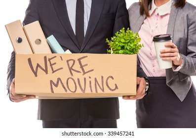 Young happy businessman and a business woman with boxes for moving into a new office. Studio shot, isolated on a white background