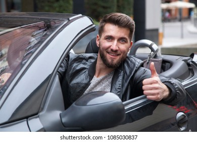 Young happy businessman in a cabriolet is pointing his thumb up.