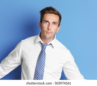 Young happy businessman on blue background