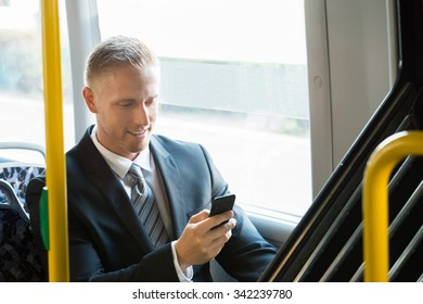 Young Happy Businessman Sitting In Tram Using Cellphone