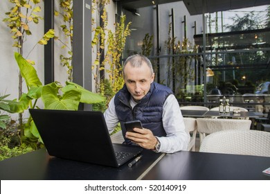 Young happy businessman smiling while reading his smartphone. Portrait of smiling business man reading message with smartphone in office. Man working. man using internet on smart phone and laptop