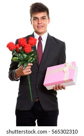 Young happy businessman smiling while holding red roses and gift box ready for Valentine's day