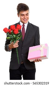 Young happy businessman smiling while holding red roses and looking at gift box ready for Valentine's day