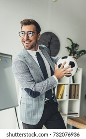 young happy businessman with soccer ball at office