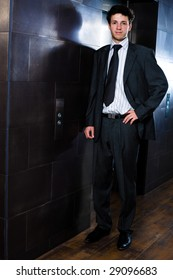 Young happy businessman standing at office in front of elevator.