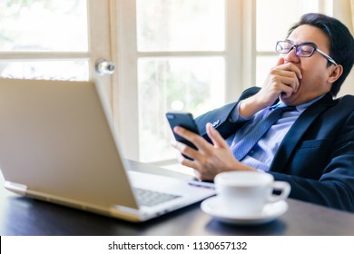 Young happy businessman using his smartphone and sleepy while gag on office desk. Portrait of business executive man using laptop in office on lazy day.