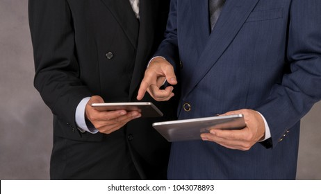 Young happy businessmen dressed in suit working on his tablet or touchpad in office.