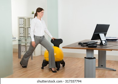 Young Happy Businesswoman Exercising With Pilates Ball On Chair In Office