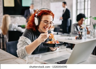 Young happy businesswoman with headphones eating salad and her office desk. There are people in the background.