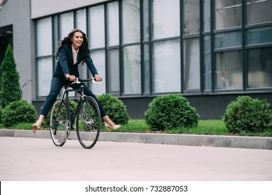 young happy businesswoman riding vintage bicycle