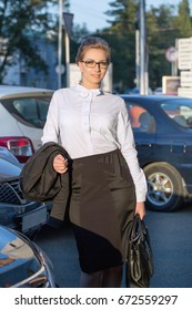 Young happy businesswoman standing near the business office