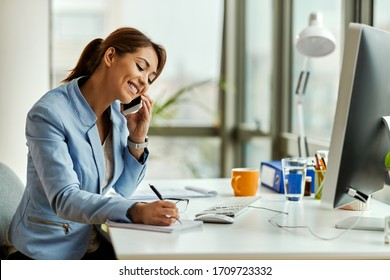 Young happy businesswoman talking on mobile phone and taking notes in the office.  - Shutterstock ID 1709723332