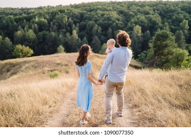 Young happy caucasian couple with little baby boy. Parents and son walking and having fun together. Mother and father playing with toddler outdoors. Family, parenthood, childhood, happiness concept.